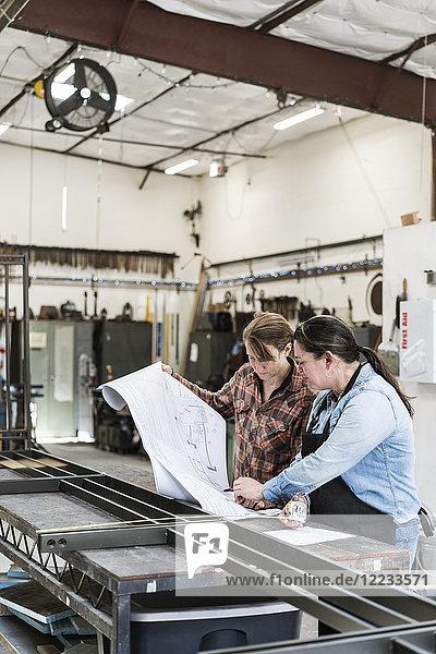 Zwei Frauen stehen an der Werkbank in einer Metallwerkstatt und schauen sich technische Entwürfe an.