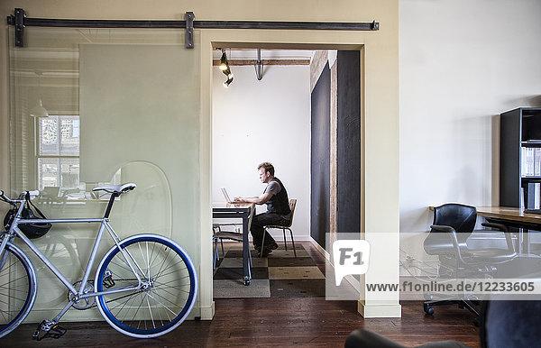Kaukasischer Mann  der in einem kleinen Konferenzraum an einem Laptop-Computer arbeitet.