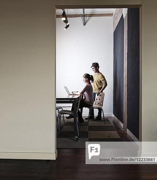 Hispanoamerikaner und Kaukasierin  die in einem kleinen Konferenzraum an einem Laptop-Computer arbeiten.