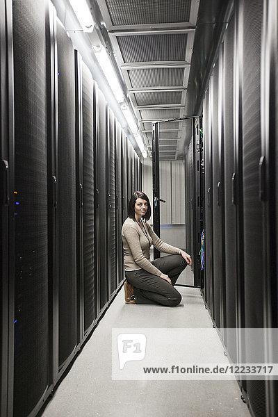 Kaukasische Technikerin  die auf Computerservern in einer Serverfarm arbeitet.