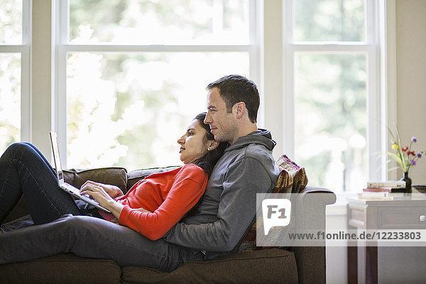 Kaukasischer Mann und gemischtrassige kaukasische Frau  die einen Laptop benutzen  während sie zu Hause auf einer Couch sitzen.