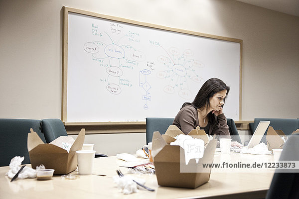 Caucasian woman working through lunch at a conference room table.