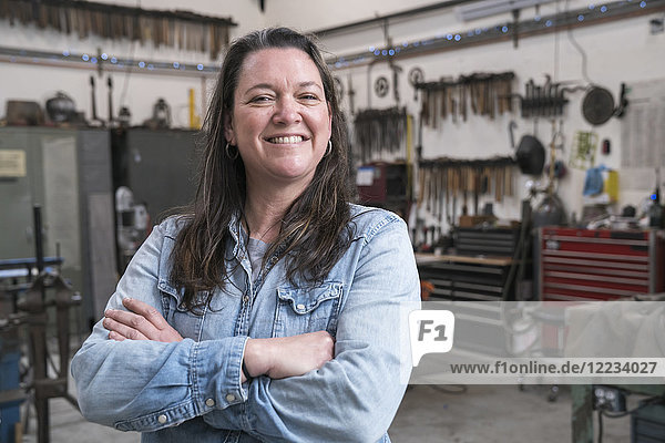 Woman with brown hair wearing Denim shirt standing in metal workshop  smiling at camera.