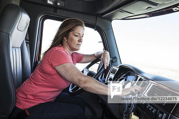 Kaukasische Fahrerin parkte und benutzte das GPS-Kartierungsgerät in der Kabine eines Lastwagens.