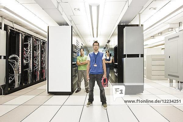 Portrait von drei multiethnischen Technikern  die in einem großen Computer-Serverraum arbeiten.