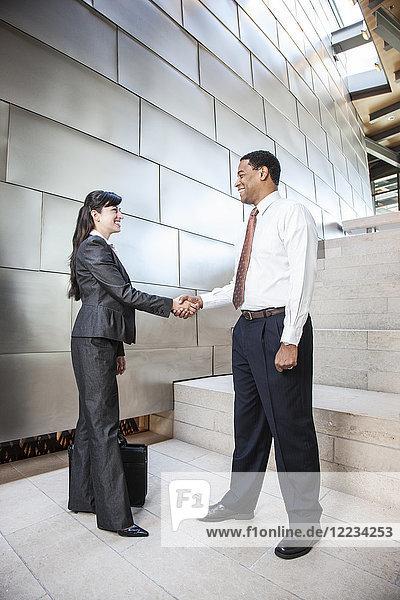 Schwarzer Geschäftsmann und hispanische Geschäftsfrau in der Lobby eines großen Bürogebäudes.
