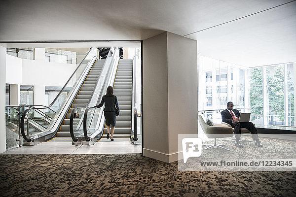Geschäftsfrau auf einer Rolltreppe in einem großen Geschäftszentrum.