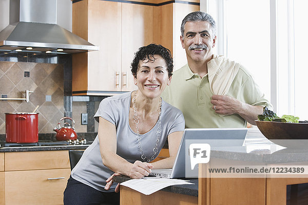 Caucasian man and woman in a kitchen using a laptop.