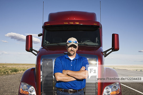 Portrait of a Caucasian man driver and his commercial truck.