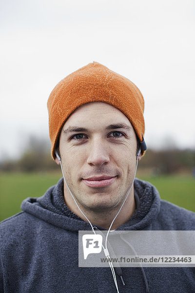 Portrait of a Caucasian man in an orange beanie hat.