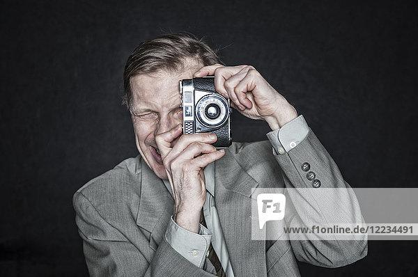 Studio portrait of Caucasian man actor using a camera  squinting and focussing.