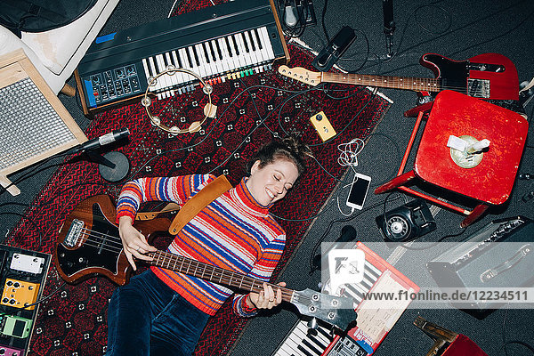 High angle view of smiling woman playing guitar while lying on carpet at studio