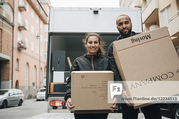 Portrait of male and female messengers carrying cardboard boxes while standing against delivery van in city