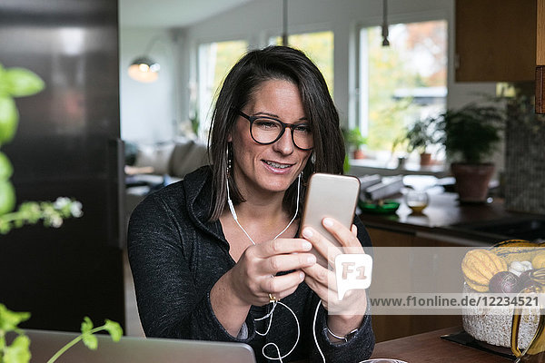 Female design professional using mobile phone while sitting in home office