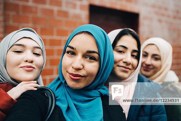 Portrait of smiling Muslim friends against building in city