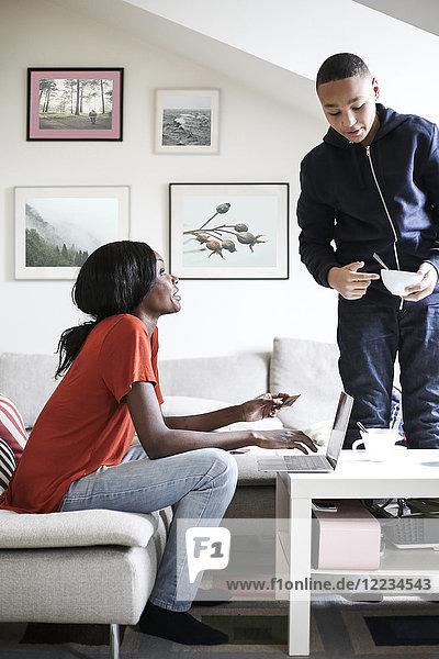 Mutter benutzt Kreditkarte  um online einzukaufen  während sie mit dem Sohn spricht  der die Frühstücksschale im Wohnzimmer hält.