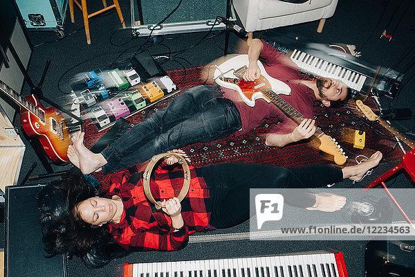 Hochwinkelansicht von männlichen und weiblichen Freunden  die im Studio auf dem Boden liegend Instrumente spielen.