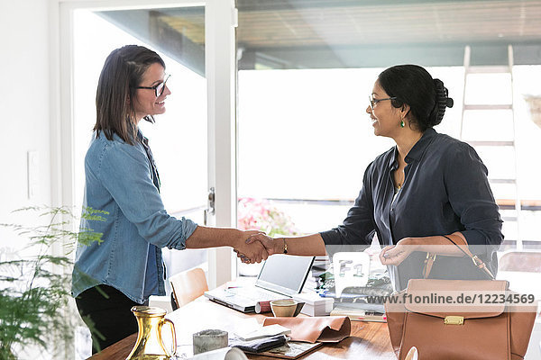 Weibliche Kollegen beim Händeschütteln am Tisch im Home-Office