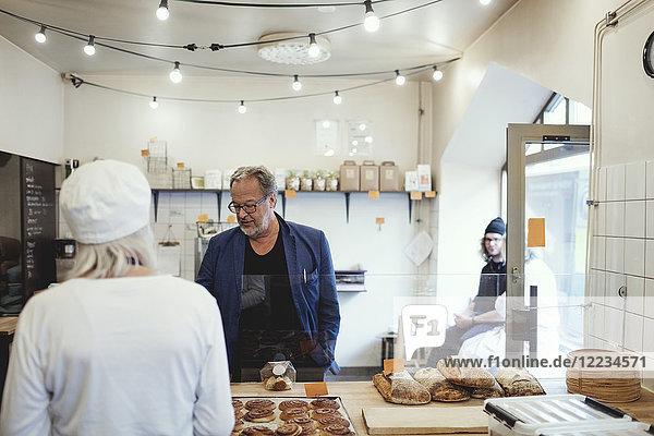 Männlicher Kunde kauft Lebensmittel vom Besitzer in der Bäckerei