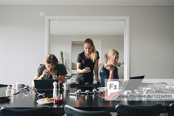 Familie mit Technologien am Esstisch im Zimmer