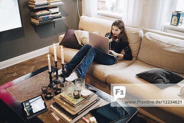 Hochwinkelansicht des Mädchens mit Handy und Laptop im Sitzen auf dem Sofa