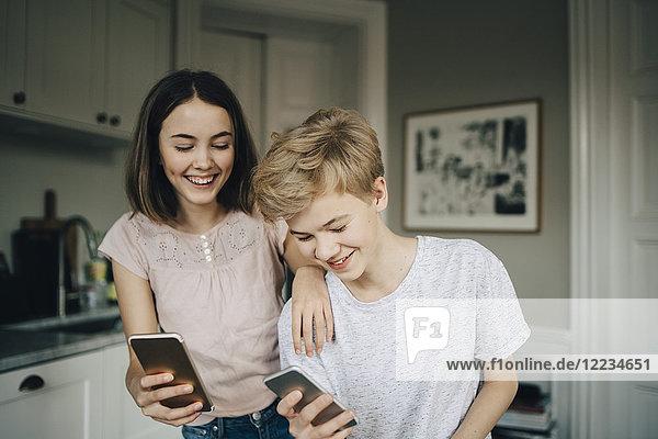 Glückliche Freunde und Freundinnen halten Smartphones zu Hause in der Küche.