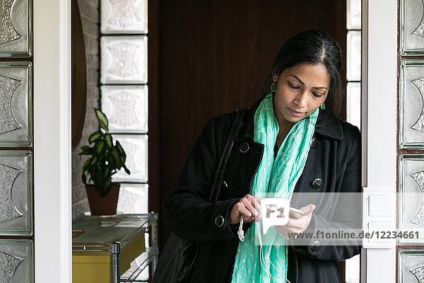Geschäftsfrau mit Handy im Home-Office