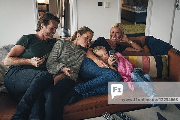Lächelnde Familie  die den Jungen mit dem Handy ansieht  während er zu Hause auf dem Sofa sitzt.