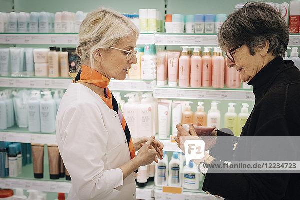 Seitenansicht der älteren Kundin und Inhaberin  die im Apothekenladen Medikamente aufbewahrt.
