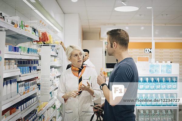 Männliche Kundin im Gespräch mit Besitzerin im Apothekengeschäft
