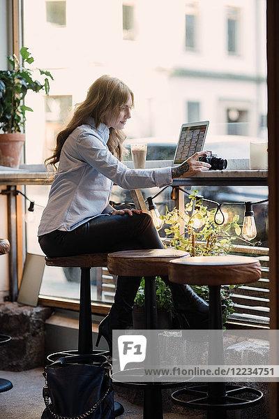 Volle Länge der jungen Frau  die die Kamera hält  während sie mit dem Laptop im Cafe sitzt.