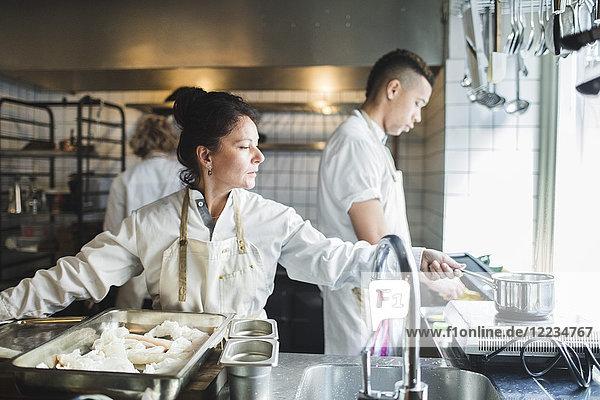 Reife Köchin kocht auf dem Herd und arbeitet in der Küche gegen Kollegen