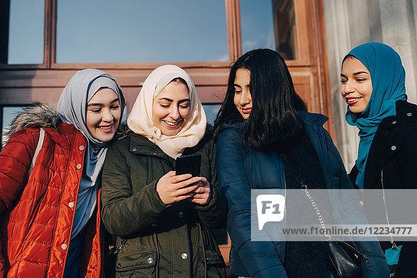 Happy female Muslim friends sharing smart phone standing against entrance door in city