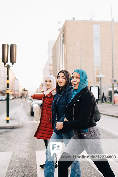 Side view of portrait of smiling female friends crossing street in city