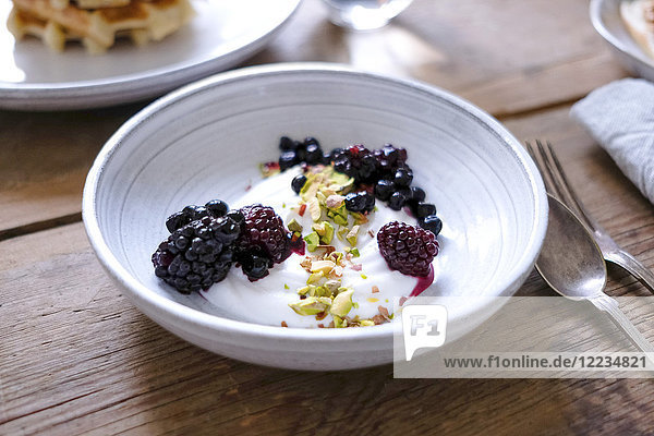 Close-up of yogurt with blackberries and pistachios in bowl at table