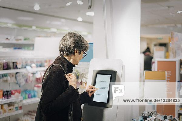 Seitenansicht der Seniorin am Kiosk in der Apotheke