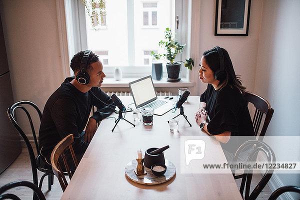 Hochwinkelansicht von Bloggern  die über Mikrofone und Kopfhörer am Tisch sprechen.