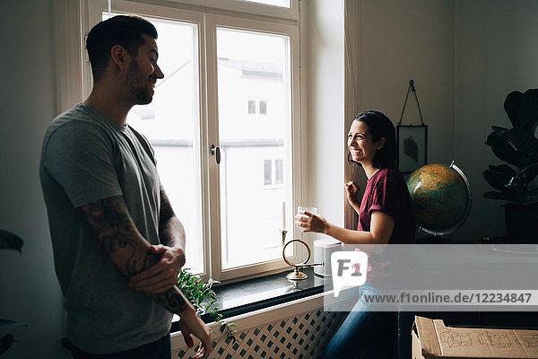 Lächelndes Paar  das am Fenster des neuen Hauses steht und redet