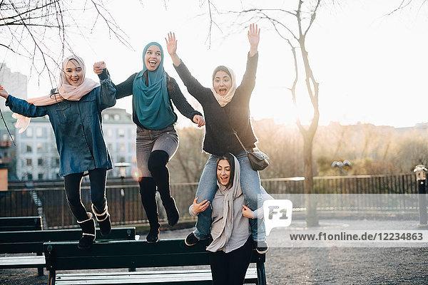 Cheerful multi-ethnic female friends enjoying against clear sky