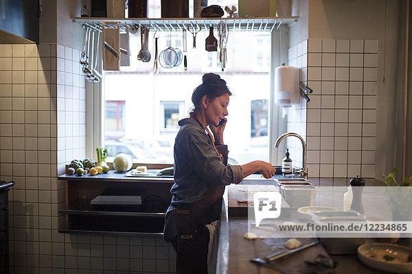 Seitenansicht des reifen Küchenchefs beim Zubereiten von Speisen in der Restaurantküche.