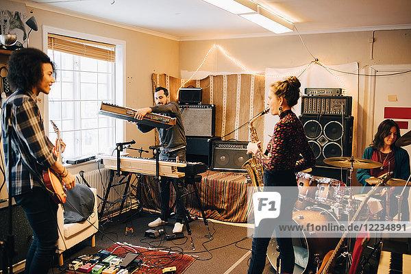 Männliche und weibliche Freunde spielen verschiedene Instrumente im Tonstudio.