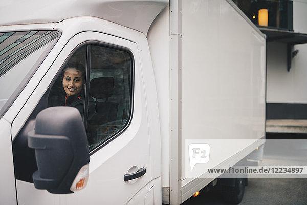Lächelnde Arbeiterin fährt weißen Lieferwagen in der Stadt