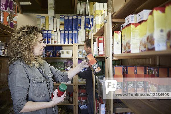 Seitenansicht des reifen Freiwilligen bei der Untersuchung von Lebensmitteln im Lagerhaus