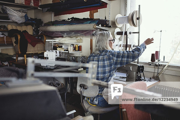 Senior owner using sewing machine at table in workshop