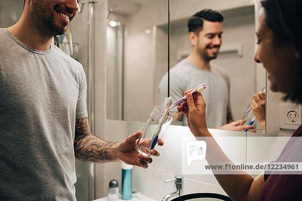 Lächelndes Paar  das Zahnbürsten in einem Behälter mit Spiegel im Badezimmer anordnet.