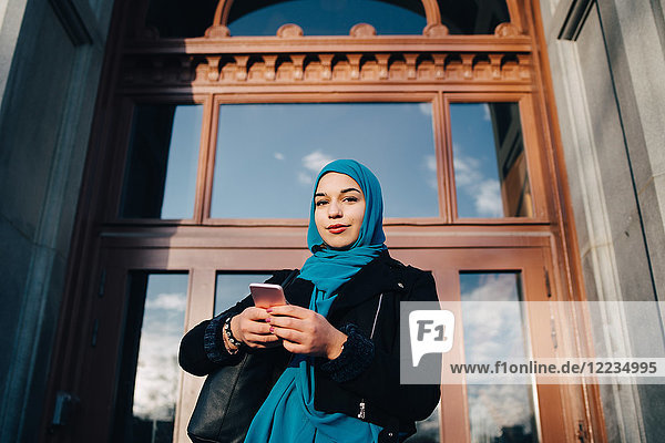 Low angle portrait of confident young Muslim woman standing with smart phone against entrance door