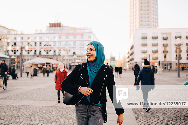 Smiling young Muslim woman wearing hijab walking on footpath in city