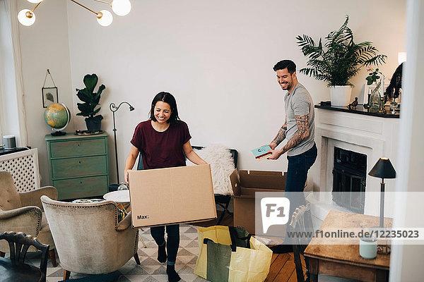 Glückliches Paar beim Auspacken von Kisten im Wohnzimmer im neuen Zuhause