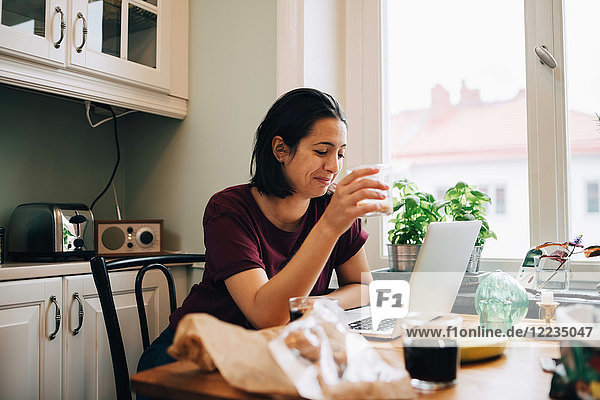 Frau mit Laptop beim Trinken am Esstisch in der Küche