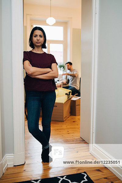 Porträt einer mittleren erwachsenen Frau mit gekreuzten Armen  die sich an der Tür des neuen Hauses lehnt